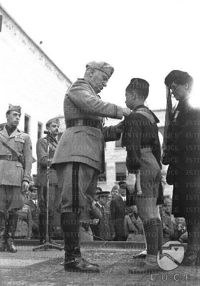 Mussolini consegna una medaglia alla memoria all'orfano di un caduto nel corso delle celebrazioni per il XVIII Annuale della Milizia Universitaria  ATTUALITA/A40-143/A00142004.JPG