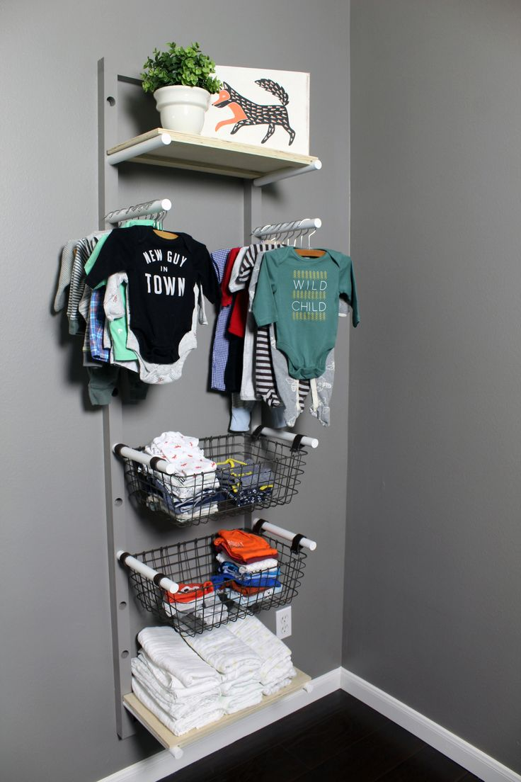 No closet? No problem! Install a DIY clothing rack using dowels and attached baskets for storing baby clothes.