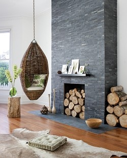 Perhaps take out the current built in's? Add drywall on each side of the fireplace and add slate from floor to ceiling...