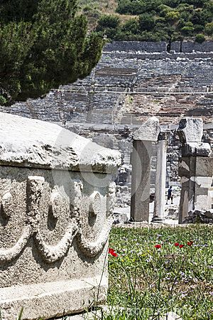 A white marble sarcophagus is on the grass. On the background the famous amphitheater of Ephesus is visible.