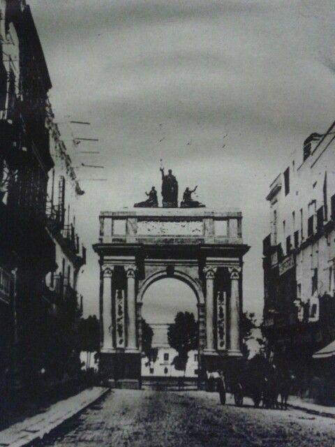 Arco del Emperador, levantado en la calle de Plateros, hoy Madero, con motivo de la entrada de Maximiliano y Carlota a la Ciudad de México.  Al fondo se aprecia el Palacio Nacional y la plancha del Zócalo con escasos árboles.  Imagen de 1864