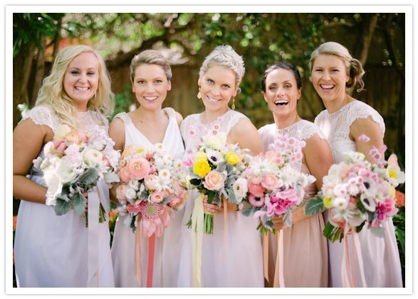 bridesmaids in hues of pink and peach ...with all those flowers!!