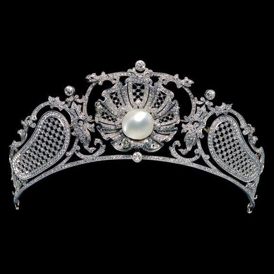 an unusual piece from 1907, featuring a central button pearl within a diamond shell motif, which detaches to form a brooch, with flanking 'kidney-shaped' diamond lattices, all linked by foliate scrolls