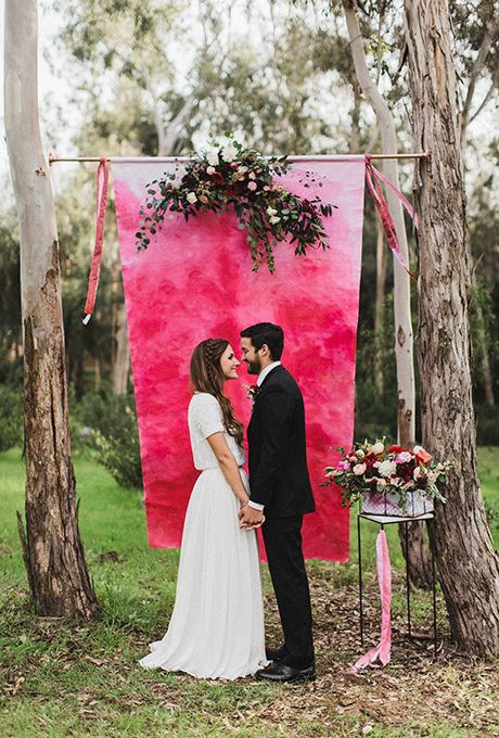 Brides.com: . A punchy-hued ombré backdrop with hanging flower garland.