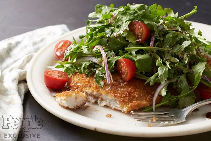 Drew Barrymore's Halibut Milanese 1 box (8 oz. container) cherry tomatoes, halved ½ red onion, thinly sliced 1 bunch arugula ¼ cup plus 1 tbsp. extra-virgin olive oil 2 tbsp. balsamic vinegar ½ tsp. salt ¼ tsp. freshly ground black pepper 2 (4-6 oz.) halibut steak fillets 2 eggs, lightly beaten 1 cup panko bread crumbs 2 tbsp. butter