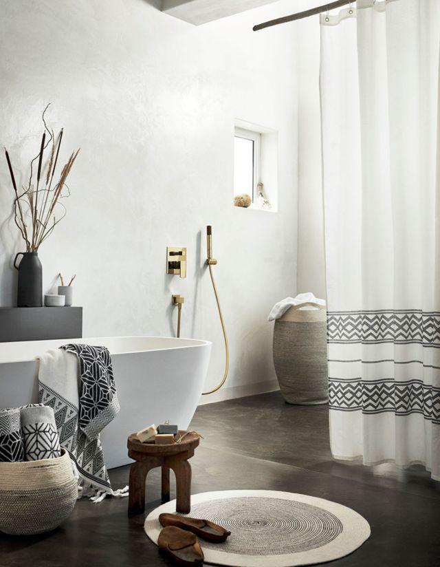 Le style ethnique chic gagne la salle de bains - vase en pierre noir, paniers, serviettes de bain, tapis rond en jute et rideau chez H&M Home