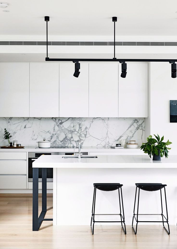 Black and white monochrome kitchen: handleless white cabinets and benchtops, grey marble splashback, black bar stools, black spotlights on suspended ceiling track, timber floorboards