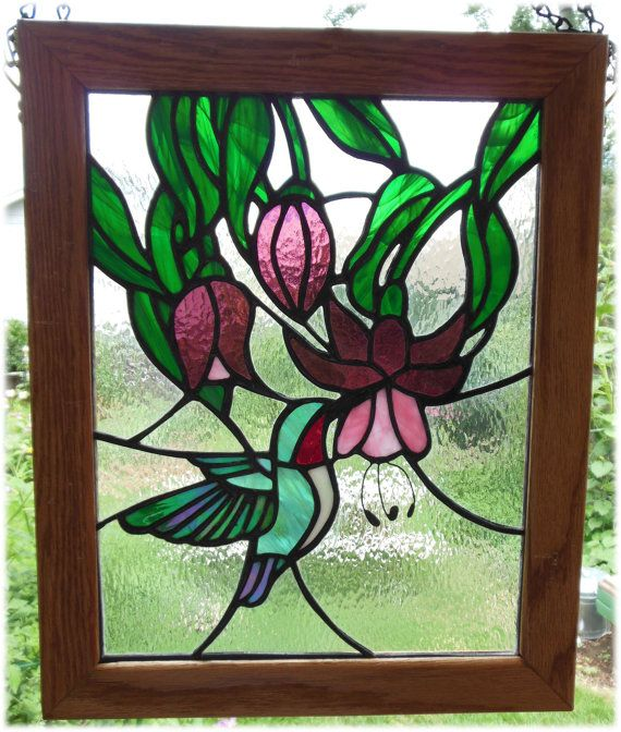 """An amazing show of light comes through this piece featuring a hummingbird and three fuchsia flowers. This is an original copper foil design. The outside measurements of the oak frame are 13.5"""" x 16.75""""."""