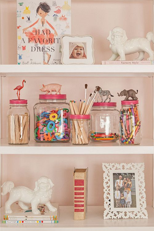 Craft supply jars and white shelves.
