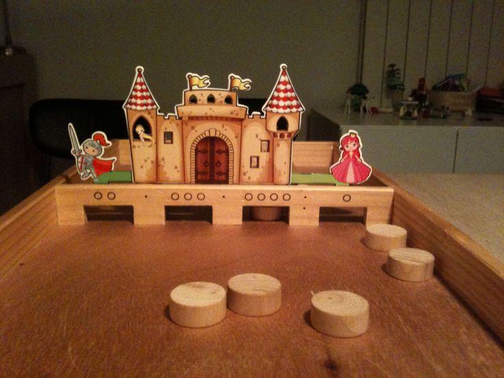 Maak van een sjoelbak een kasteelspel: wie sjoelt de meeste goudstukken in het kasteel. Gemaakt met onderdelen uit de ridder en prinses kijkdoos van Action