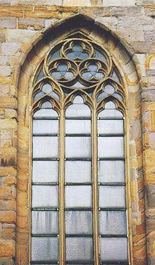 Maswerk (w postaci trójliści) betonowa konstrukcja w gornej czesci okns eypelnona szklem