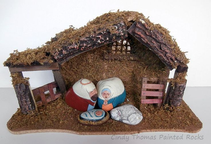 Nativity set painted on rocks and displayed in a store-bought stable