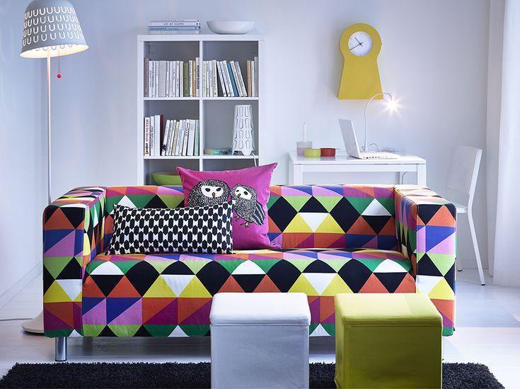 Ein Wohnzimmer Mit 2er Sofa Buntem Bezug Aus Baumwolle Und Zwei Hockern In Weiss