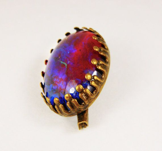 How about a beautiful dragons breath fire opal for your scarf? Or maybe your hat? Or maybe for your shirt collar?  This beautiful dragons breath fire opal brooch is just that...beautiful. They are made of synthetic glass to re-create the effects of an opal, shinning from red to vibrant blue in the sun.  The size of this dragons breath fire opal measures 1.8cmx1.3cm or .7x.5.  Lastly, the brooch setting is made of antique bronze alloy and has been fashioned in a classy vintage inspired way…