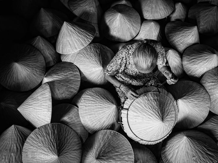 """Picture of a woman making conical hats out of palm leaves in Duc Hoa, Vietnam 