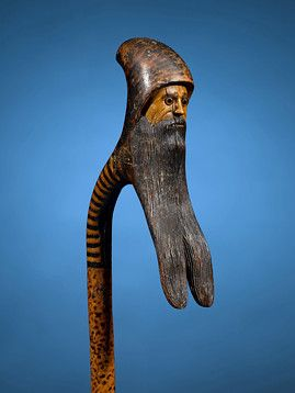 Beard Man Folk Art Cane  The top of this snakewood folk art cane is meticulously carved in the form of a bearded man. Dynamic spotting and stripping distinguish this stick, while glass eye accents add a decorative touch to the face.