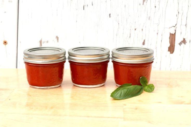 Trois pots mason de concentré de tomate et des feuilles de basilic sur une table en bois