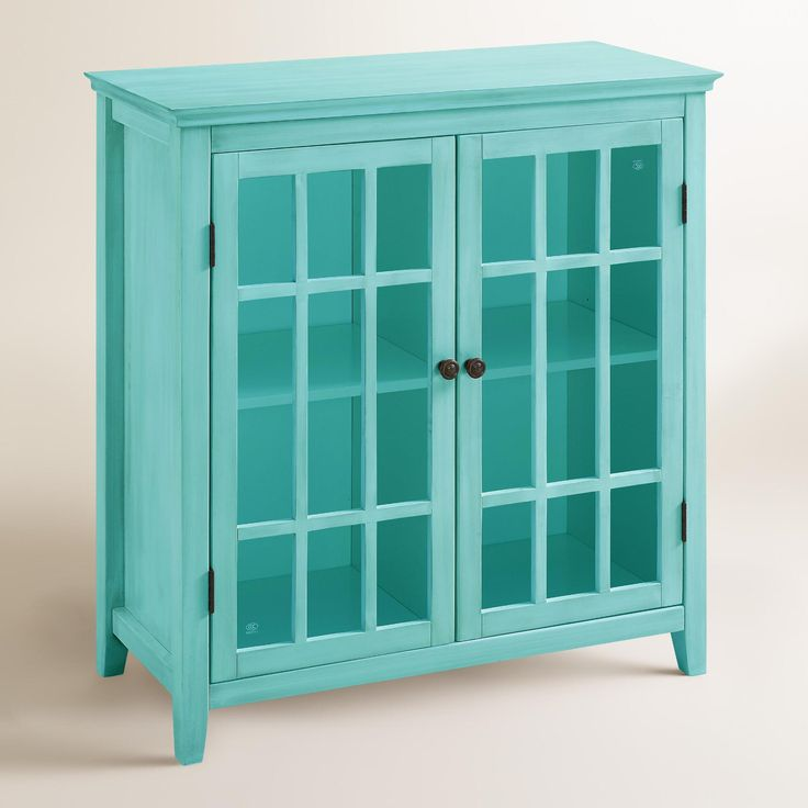 Crafted of pine wood with a turquoise finish and antique bronze accents, our chic, contemporary media cabinet features glass panel doors that open to reveal ample storage space divided into four compartments.