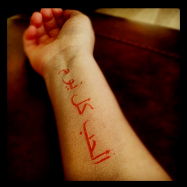 """Arabic tattoo I like the red, not the saying """"Love Each Day"""""""