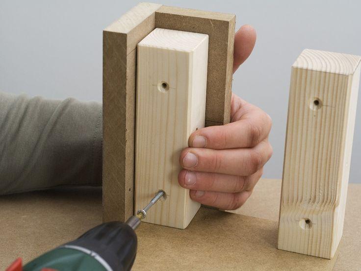 Pasul 4: Îmbinarea picioarelor tip colţar cu baza Aşezaţi baza formată din placa suport şi barele de legătură pe suprafaţa de lucru a.i. barele să fie îndreptate în sus. Puneţi un picior tip colţar confecţionat la Pasul 1 pe barele de legătură. Înşurubaţi piciorul tip colţar cu barele de legătură, folosind maşina de înşurubat cu acumulator şi şuruburile cu cap înecat de 4 x 50 mm. Pentru cele două şuruburi de pe partea interioară, desprindeţi din nou picioarele de masă de placa suport.