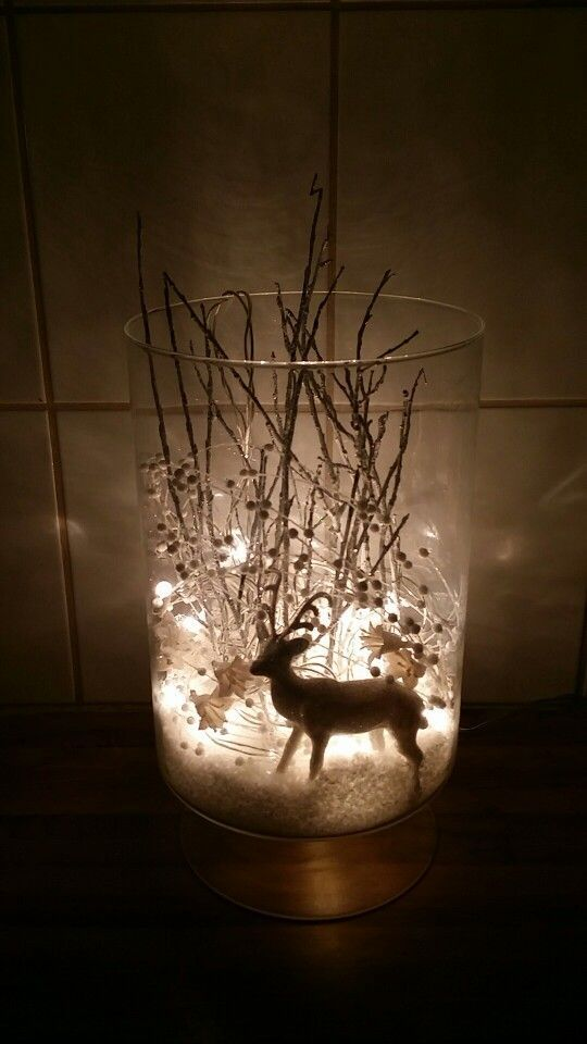 I took a vase, fake snow, a white glimmer reindeer, some silver tree branches, a…