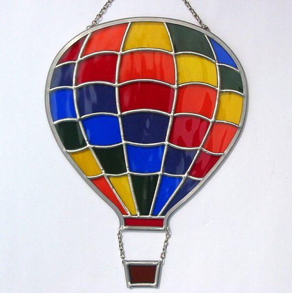 Suncatcher ballon air chaud darc en ciel vitrail fabriqués à la main dans la méthode Tiffany à laide de belle Waterglass texturé verre fabriquées par la société de verre Spectrum. Waterglass a une texture douce qui ressemble à leau sur un lac. Les pièces ont été disposés de sorte quil semble que le ballon est gonflé et prêt à en altitude. Le panier a été conçu à laide dun verre texturé brillant de couleur ambre.  Les morceaux de verre ont été découpés à la main, enroulés avec une feuille de…