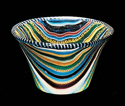 A brilliantly colored glass cup was made in the Roman Empire from ribbons of glass in about the 1st century AD.