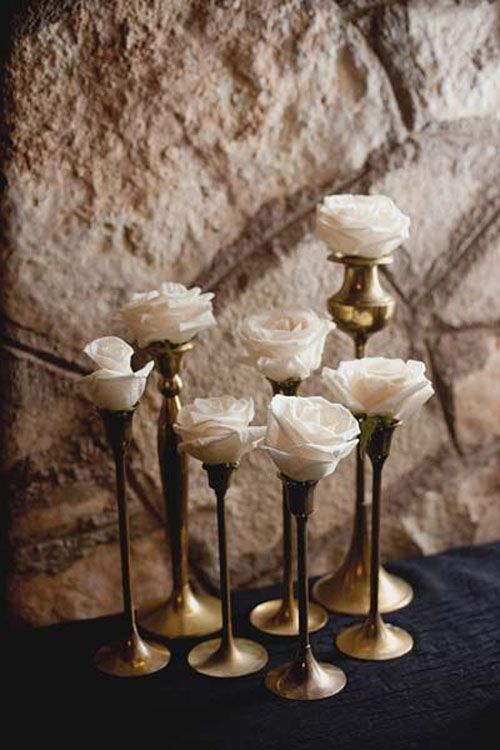 simple wedding centerpieces: this a great idea for a renaissance wedding. Use every size candle holder you can find and stick a rose or two in it. This has a fantastic look to it.