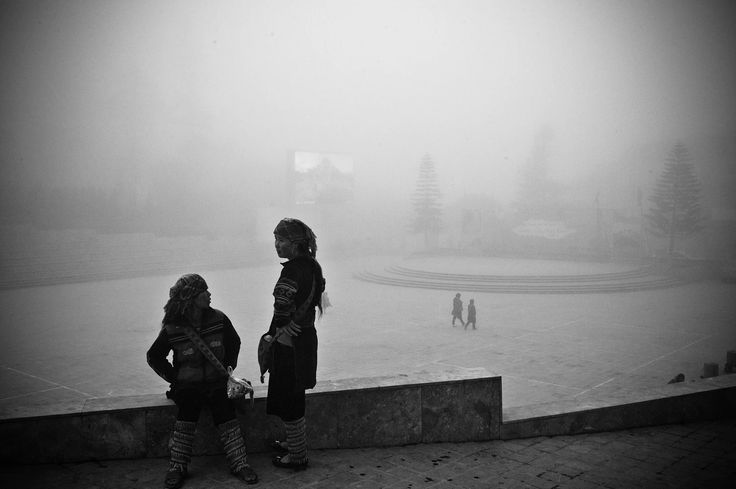 #Sapa #Holiday #Travelmagazine: A pair of young girls of H'mong tribal people are in deep conversation in the city of Sa Pa, in a foggy winter afternoon.