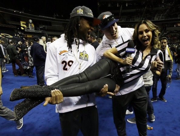Denver Broncos' Bradley Roby (29) and Jeff Heuerman hold up reporter Keltie Knight during Opening Night for the NFL Super Bowl 50 football game Monday, Feb. 1, 2016, in San Jose, Calif. (AP Photo/Jeff Chiu)