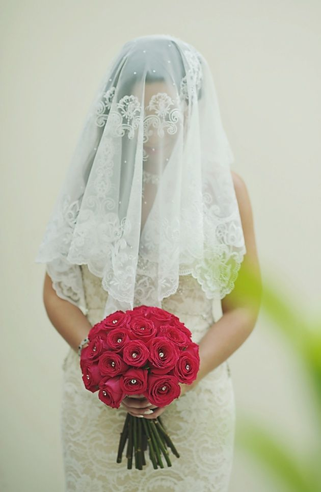 The bridal veil is a symbol of the importance of the soul's beauty over  physical beauty. Dark red roses bouquet. Jewish Greek wedding with Stella and Moscha Weddings. Photo by Thanasis Kaiafas