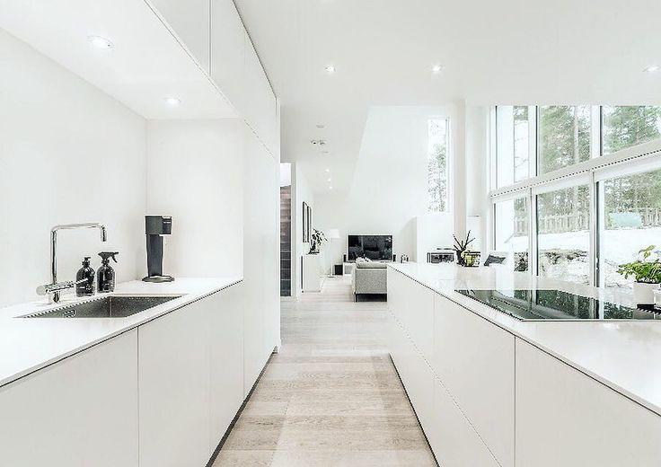 Pelkistettyä ja modernia valkoista keittiössä, joka jatkuu yhtenäisenä avoimena tilana olohuoneeksi.