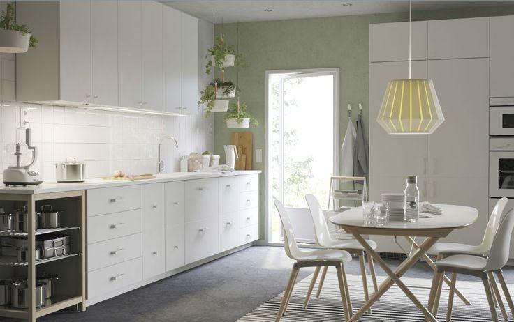 Una cocina blanca grande con encimera blanca, tiradores y pomos. Combinado con una campana extractora en acero inoxidable, un horno blanco y un microondas blanco.