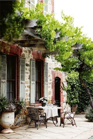 Wicker furniture and anduze urn planter vase under grape vine