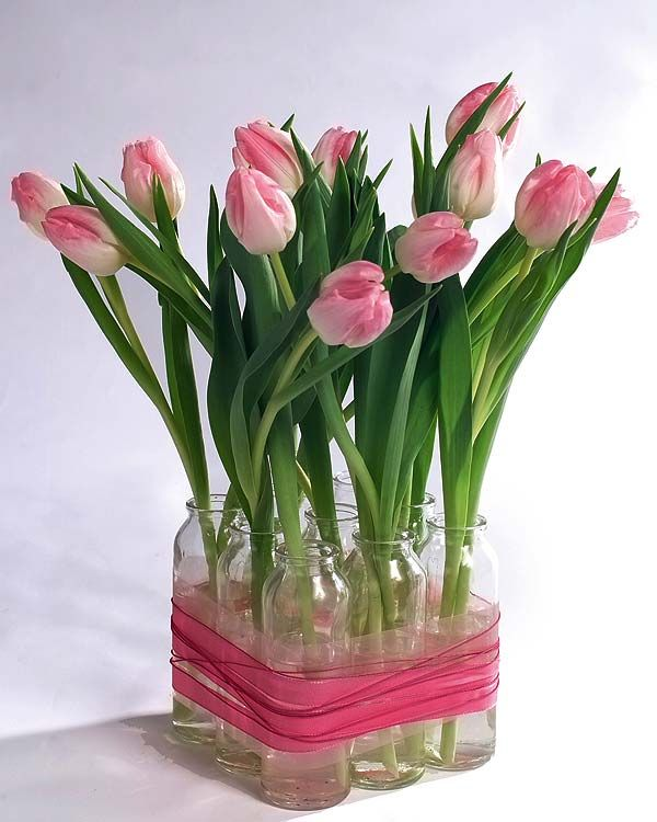Cool idea...individual flowers in glass bottles tied together with an accent ribbon to form a square centerpiece. The tulips and the ribbon make this version look work for a bridal shower or bridal luncheon. But switch the flowers out for blush roses or dahlias and a creamy ribbon and it would be perfect for a reception.