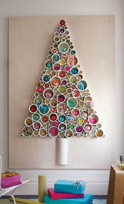 PVC kerstboom. Zaag pvc buizen van verschillende doorsnede in kleine stukken. Stukjes pvc opplakken (verschillende maten naast elkaar) op stevige ondergrond in vorm kerstboom. In de rondjes kerstballen plakken.