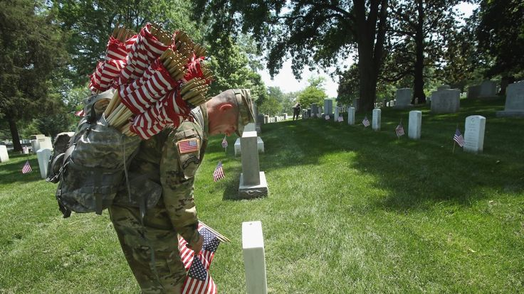 WASHINGTON, DC - MAY 26: Specialist Jose Barreiro, of the 3rd U.S. Infantry Regiment, 'The Old Guard,' places a flag at a grave site during the 'Flags-In' ceremony May 26, 2016 at Arlington National Cemetery in Arlington, Virginia. A small American flag was placed one foot in front of more than 220,000 graves in the cemetery to mark Memorial Day. (Photo by Mark Wilson/Getty Images)