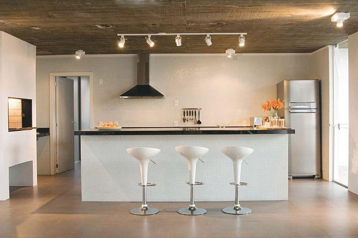 """O teto de concreto aparente contrasta com as luminárias brancas (Interlight). """"Presa direto na laje, a régua com cinco spots pontua o balcão. Lâmpadas PAR 20 deixam a iluminação mais quente e agradável"""". As demais luminárias, com o mesmo tipo de efeito, servem de luz geral."""