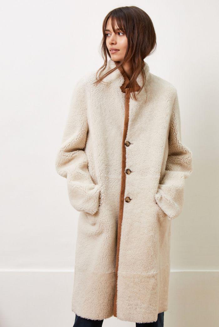 Manteau long camel en peau lainée réversible. Deux poches plaquées sur le  devant. Fermeture par 3 boutons. 42b2c093332