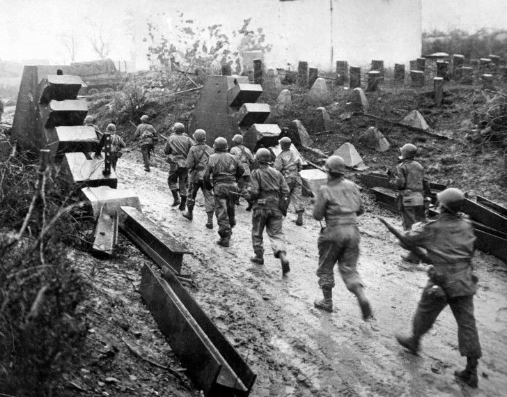 American soldiers crossing on his section of the front line of defence of The Siegfried Line at the German border. Siegfried line consisted of anti-tank obstacles, concrete, trenches and Pillbox points. 1945