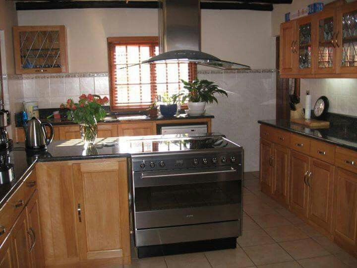 American Beech kitchen with Rustenburg black granite counter tops and lead detail on the glass doors.