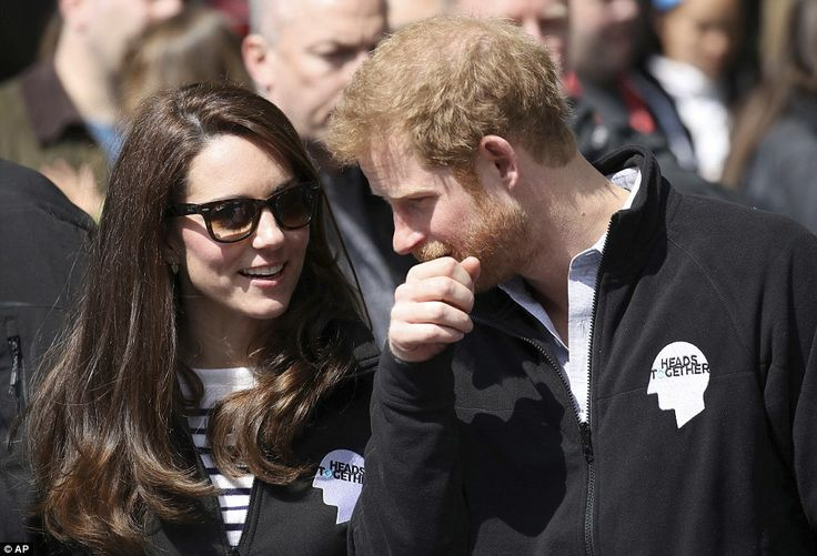 Whispers: Prince Harry leaned in close to Kate as the pair chatted quietly while watching runners whiz past in central London