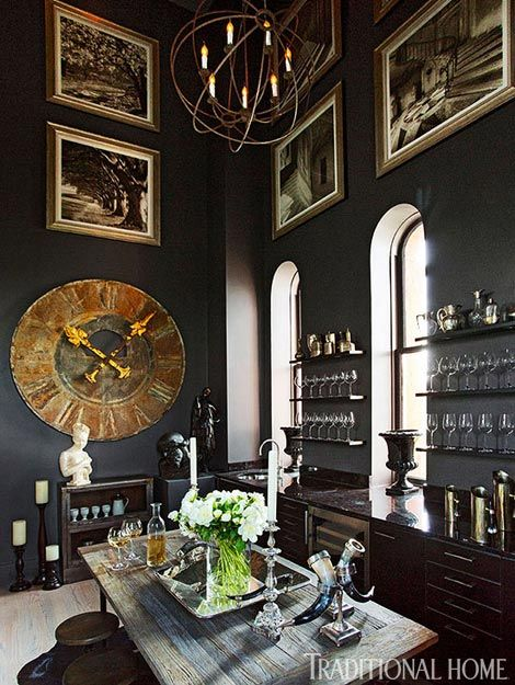 A wine room is furnished with a large antique bronze clock and dramatic wall paint from Pratt & Lambert - Traditional Home® / Photo: Eric Roth / Design: Joseph Abboud in partner with RH