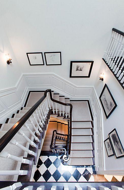 dark floors on steps with a light runner, black and white floor, white walls, black railing, white spindles