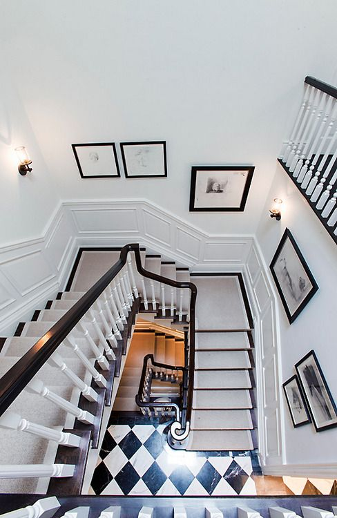 dark floors on steps with a light runner, black and white floor, white walls, black railing, white spindles