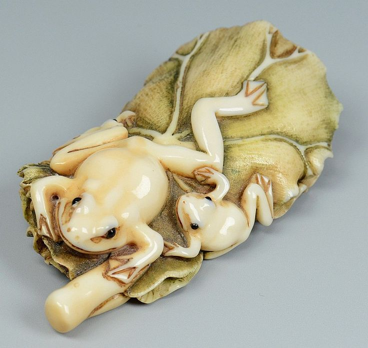 Ivory netsuke of two frogs on a stained green lily pad, early 20th century, 3 1/4 x 1 3/4""