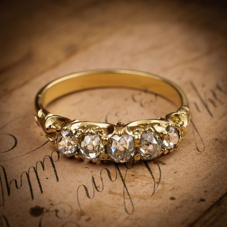 In mint condition, this antique Victorian engagement ring is a superb example of Victorian craftmanship. The half hoop design is bedecked with scrolls to it's s