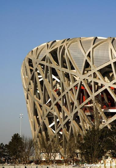 """Beijing International Stadium is a landmark building, which staged the 2008 summer Olympic Games  The stadium is considered to be the world's largest enclosed space.. It is also the world's largest steel structure with 26km of unwrapped steel used. The innovative structure was designed by Herzog & De Meuron Architekten, Arup Sport & the China Architecture Design and Research Group, & has been nicknamed the """"bird's nest"""" due to the web of twisting steel sections that form the roof"""