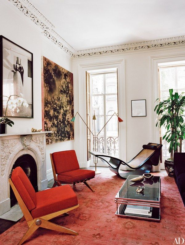 In the library of a Manhattan townhouse, 1950s Pierre Jeanneret chairs with cushions covered in a Pierre Frey velvet are paired with an Oscar Niemeyer chaise longue. The '50s floor lamp is Italian, and the rug is by ABC Carpet & Home; the large painting is by Aaron Young, and a photograph by Roman Signer is displayed above a marble mantel original to the house.