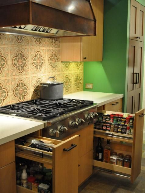 Large pullout drawers keep spices and condiments at hand in this Southwestern-themed kitchen. Mexican tiles combined with the copper hood and green walls make this range the kitchen's focal point.